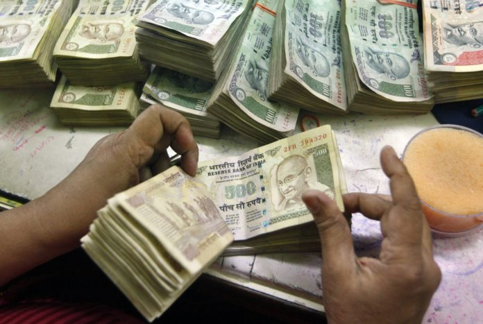 Rs 500 and Rs 1000 Notes: An employee counts Indian currency notes at a cash counter inside a bank in Kolkata